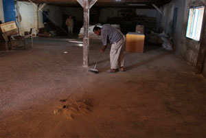 A Palestinian worker sweeps out the empty storeroom of a U.N. food distribution center in Gaza City.
