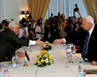 Abbas and Sharon reach across the negotiating table to shake hands.