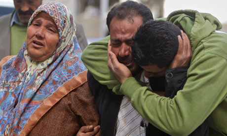Umm Ahmed Abu Rahmeh, left, and her two sons, react as the body of her son Bassem arrives at a hospital.
