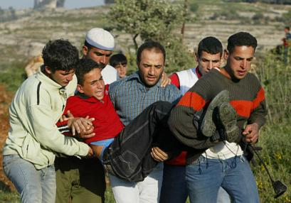 Palestinian boy is carried away after being hit by a rubber-coated steel bullet.