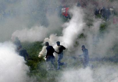 Protestors run for air through a thick cloud of tear gas.