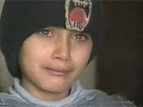 A Palestinian girl cries while her mother lies dying on the floor.