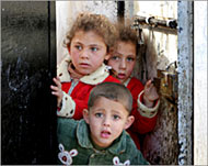 Photo of 3 small Palestinian children looking through a door.