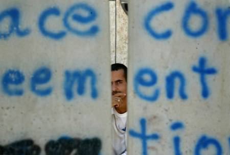 A Palestinian is seen through a gap in an unfinished part of Israel's controversial security barrier which separates east Jerusalem from the West Bank town of Abu Dis on July 9, 2004.
