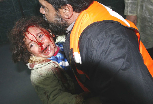 A bloodied child arrives at Shifa hospital in Gaza City after an Israeli air strike yesterday.