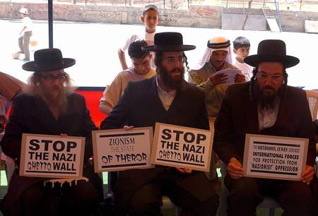 Anti-Zionist ultra-Orthodox Jews participating in a hunger strike in Jerusalem to protest against the separation wall, hold signs saying 'Stop the Nazi ghetto wall'.