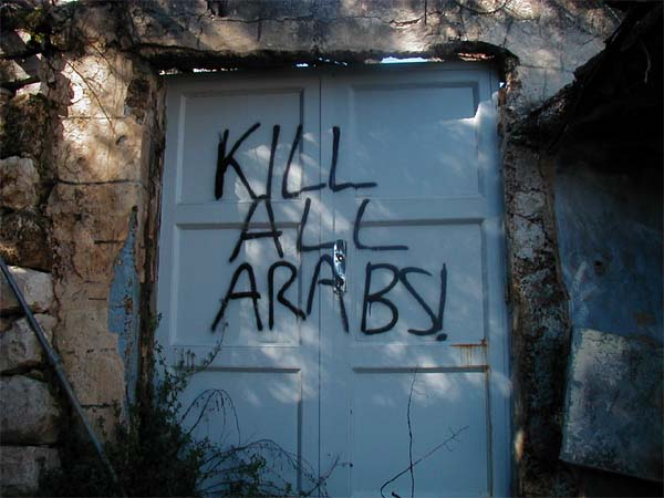Photo of settler graffiti on a door in Hebron, reading 'KILL ALL ARABS.'
