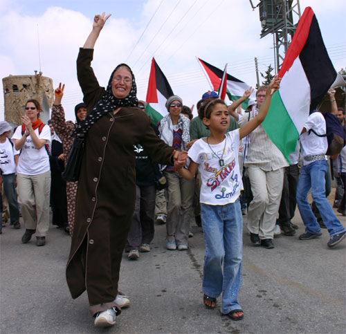 A smiling woman and child carrying a Palestinian flag lead the march.