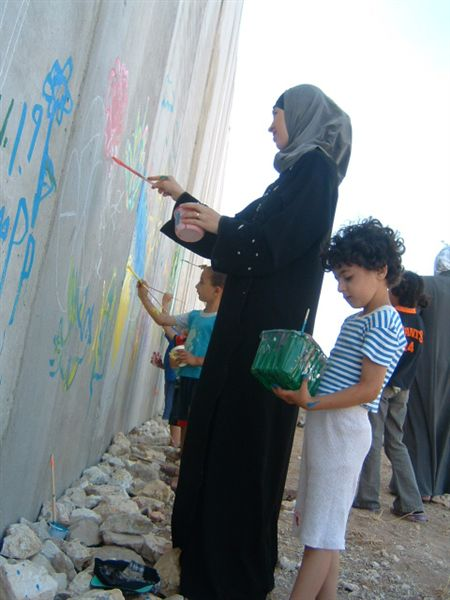 Women and children painting the Apartheid Wall.