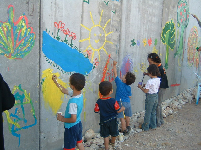 Children paint the wall with brightly colored flowers, suns, and other images.