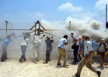 Demonstrators protesting Israel's construction of a separation barrier through Palestinian land are tear gassed.