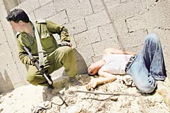 Palestinian boy who had been brutally beaten by settler youths lies against a wall; an Israeli soldier crouches near him.