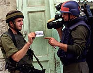Photo of an Israeli soldier checking a cameraman's press card.