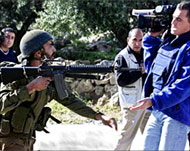 Photo of an Israeli soldier pointing his machine gun at a cameraman.