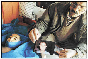 His uncle sits next to dead ten-year-old Ayman Abu-Mahdi.