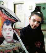 A small paralyzed girl holds a poster of her young cousin.