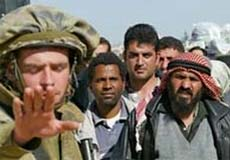 An Israeli soldier signals for people to stop. Numerous Palestinians wait behind him.