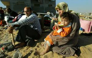 Photo of Palestinian family sitting in the rubble of their home.